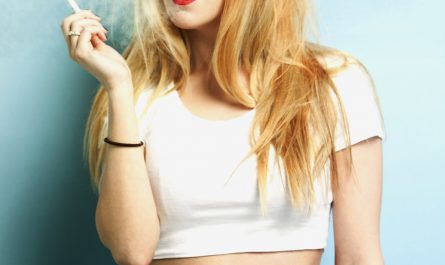 Portrait of young blond woman holding cigarette against blue background